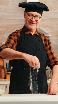 Mehltisch für ältere bäcker zum backen und backen leckerer kekse. senior chefkoch im ruhestand mit bone und schürze in einheitlicher besprengung siebsiebung von rohzutaten von hand backen hausgemachte pizza, brot