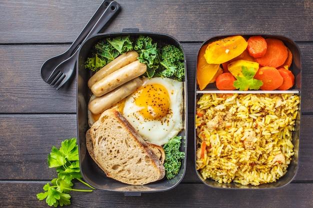 Mehlvorbereitungsbehälter mit reis mit huhn, gebackenem gemüse, eiern, würsten und salatschuß obenliegend.