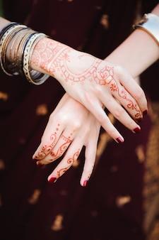 Mehndi tattoo. frauenhände mit schwarzen henna-tätowierungen. indiens nationale traditionen.