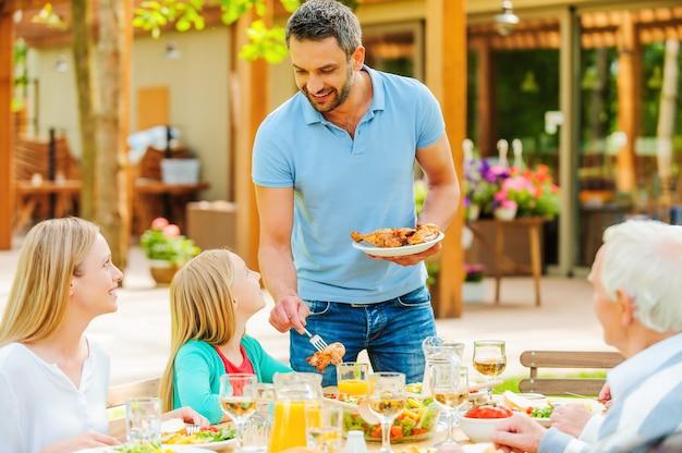 Mehr hühnchen? glückliche fünfköpfige familie, die miteinander kommuniziert und das essen genießt, während sie am esstisch im formalen garten sitzt sitting