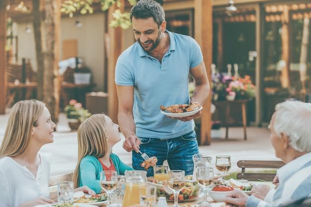Mehr hühnchen? glückliche fünfköpfige familie, die miteinander kommuniziert und das essen genießt, während sie am esstisch im formalen garten sitzt