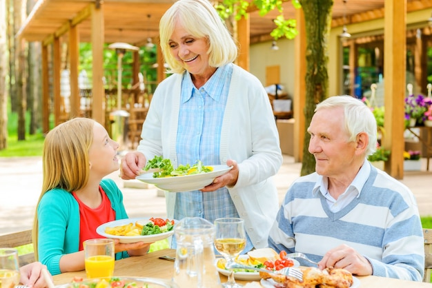 Mehr salat? fröhliche seniorin serviert frischen salat, während ihr mann und ihre enkelin im freien am esstisch sitzen dining