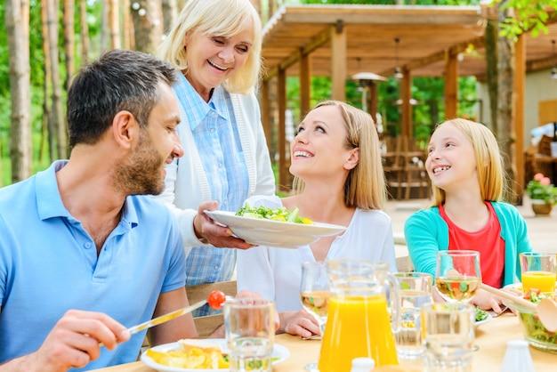 Mehr salat? glückliche familie beim gemeinsamen essen am esstisch im freien