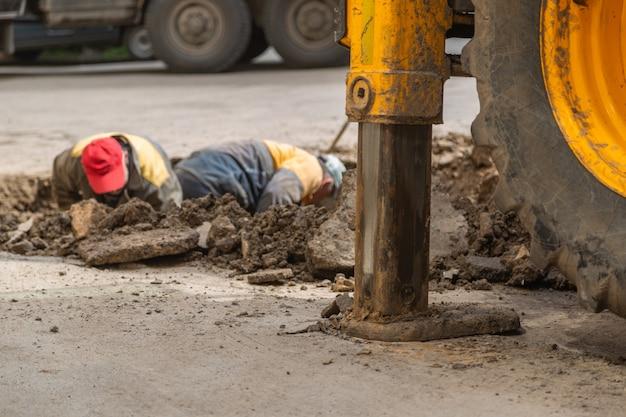 Mehrere arbeiter in overalls graben ein loch zur fehlerbehebung bei rohrleitungen