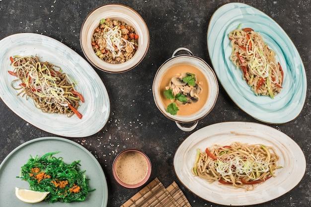 Mehrere asiatische gerichte mit nudeln, reis und seetang auf verschiedenen tellern, wobei der küchenchef auf einem dunklen hintergrund dient. ansicht von oben mit einem kopierraum. restaurant essen. flach liegen