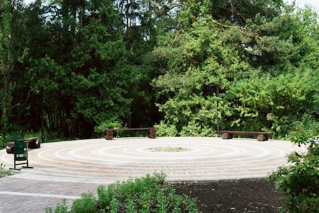 Mehrere bänke in einem grünen park. der bereich ist mit fliesen im garten gepflastert
