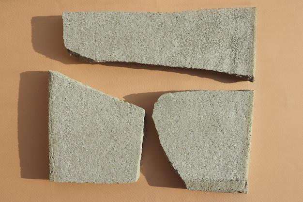 Mehrere betonspäne auf einem beigen papierhintergrund in starkem licht mit schatten. flaches layout, draufsicht.