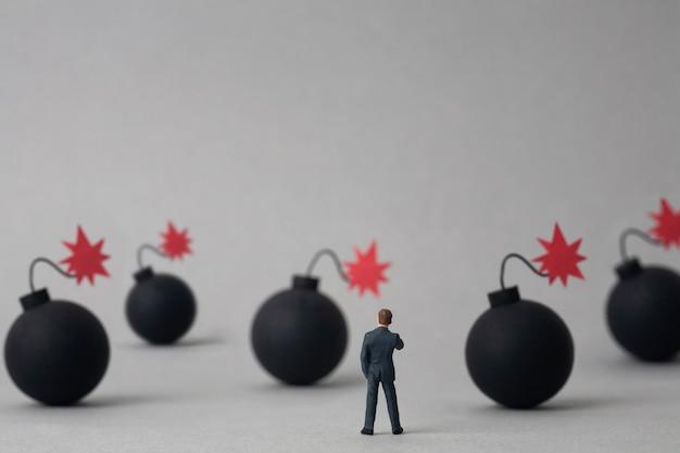 Mehrere bomben und miniaturgeschäftsmann