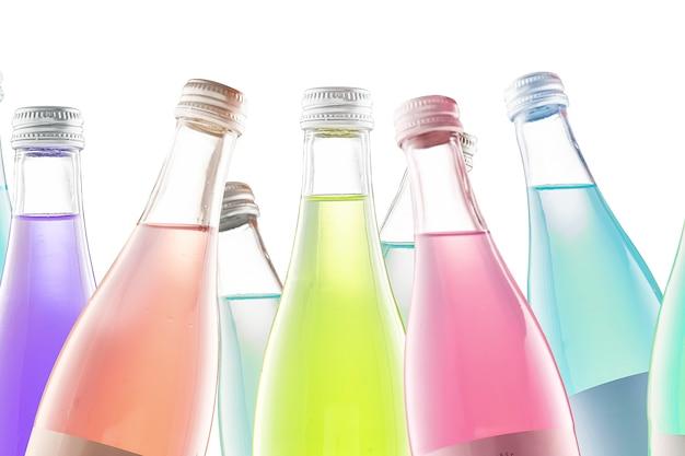 Mehrere bunte bunte flaschen mit kohlensäurehaltigen getränken und limonadenisolat