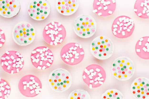 Mehrere bunte schön dekorierte muffins auf einem weißen hintergrund, draufsicht.