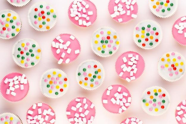 Mehrere bunte, schön dekorierte muffins auf weißem hintergrund, ansicht von oben.