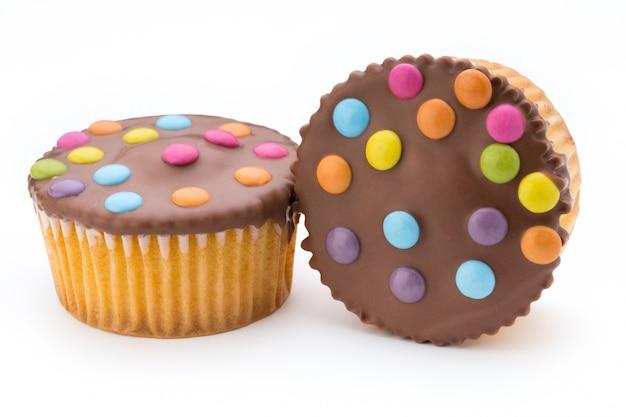 Mehrere bunte verzierte muffins auf einem weißen hintergrund.