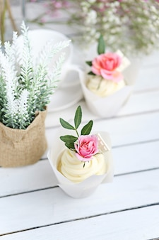 Mehrere cupcakes und muffins mit weißer buttercreme und einer lebhaften rosa rose auf einem weißen holztisch.