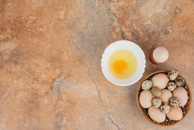 Mehrere eier mit rohem ei auf dem weißen teller in der marmoroberfläche
