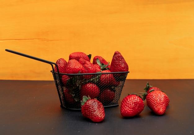 Mehrere erdbeeren in einem schwarzen korb auf einem orange hintergrund. seitenansicht.
