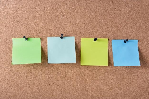 Mehrere farbige notizblätter, die an der korkplatte befestigt sind, kopieren platz
