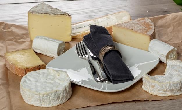 Mehrere französische käsesorten mit teller und besteck