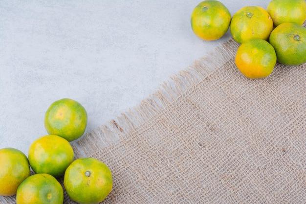 Mehrere frisch saure ganze mandarinen auf sackleinen