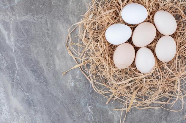 Mehrere frische hühnereier auf heu auf marmorhintergrund. foto in hoher qualität