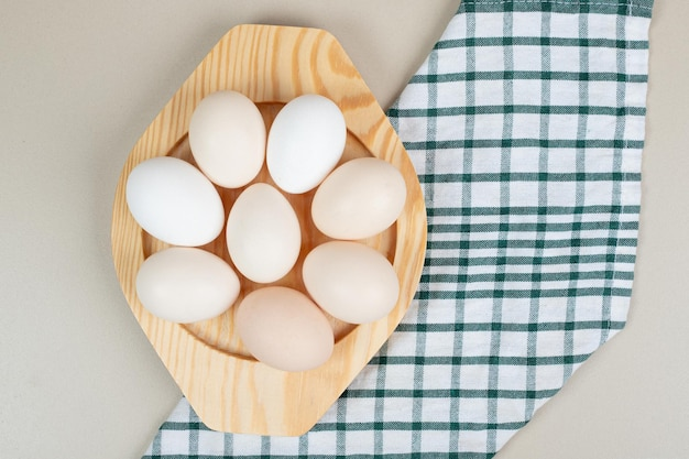 Mehrere frische weiße hühnereier auf holzteller.
