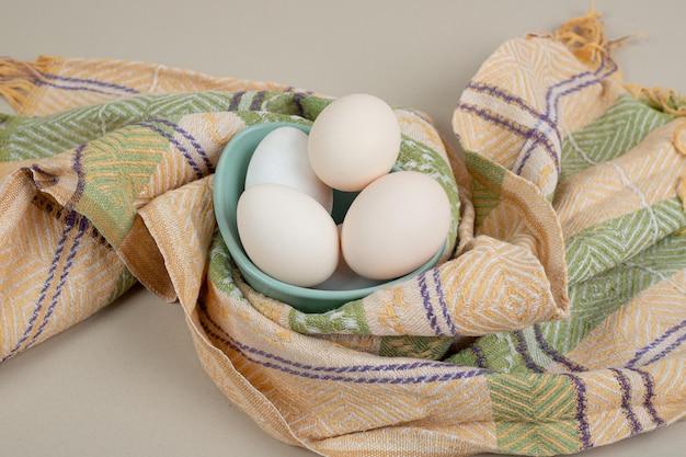Mehrere frische weiße hühnereier auf tischdecke.