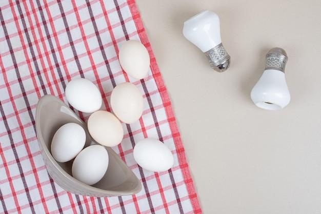Mehrere frische weiße hühnereier in der grauen platte auf tischdecke.