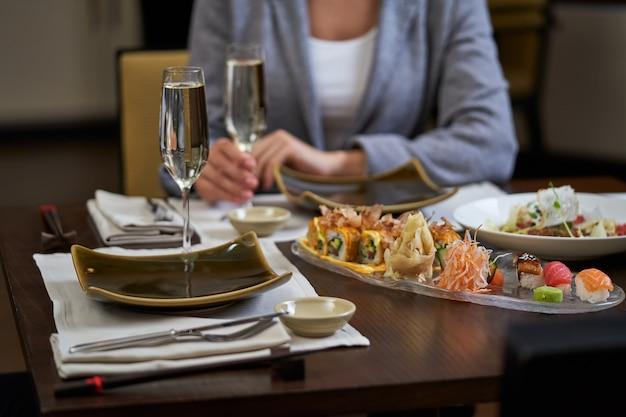 Mehrere gerichte aus fisch und garnelen stehen auf einem tisch neben zwei gläsern champagner auf servietten