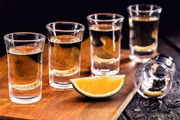 Mehrere gläser mezcal (oder mescal) ist ein exotisches alkoholisches getränk aus mexiko, destilliert, tequila-variante, mit orange verzehrt und mit einer larve darin