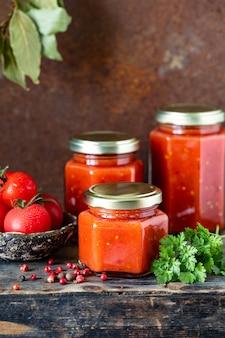 Mehrere gläser mit hausgemachter tomatensauce auf einem holztisch