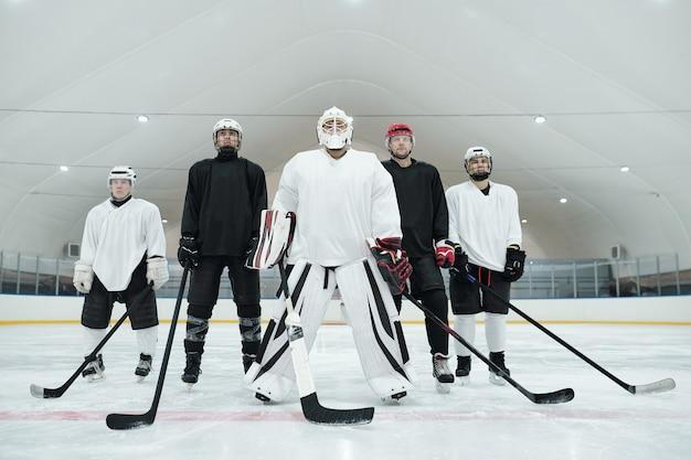 Mehrere hockeyspieler und ihr trainer in sportuniform, handschuhen, schlittschuhen und helmen stehen auf der eisbahn und halten stöcke vor sich