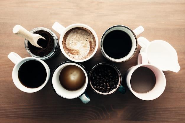Mehrere kaffeetassen, milch, bohnen und gemahlener kaffee im glas auf hölzernem hintergrund. hochwertiges foto