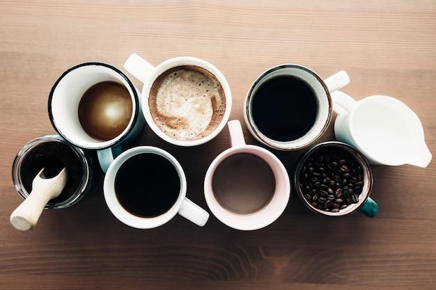 Mehrere kaffeetassen, milch, bohnen und gemahlener kaffee im glas auf hölzernem hintergrund