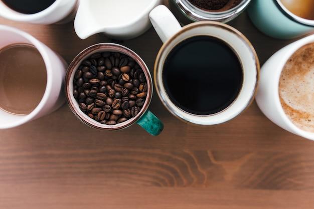 Mehrere kaffeetassen, milch, bohnen und gemahlener kaffee im glas auf holztisch. hochwertiges foto