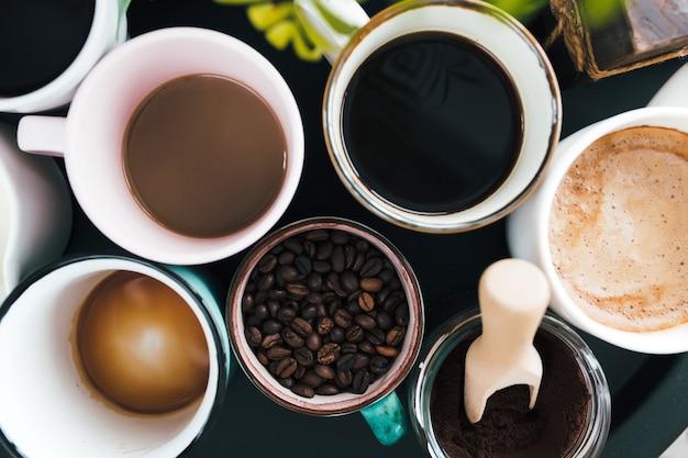 Mehrere kaffeetassen, milch, bohnen und gemahlener kaffee im glas auf schwarzem hintergrund. hochwertiges foto