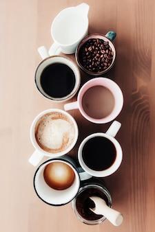 Mehrere kaffeetassen und mehrfarbige tassen mit americano, espresso, latte und cappuccino, milchglas, gerösteten kaffeebohnen in glasflasche, holzlöffel und gemahlenem kaffee im glas auf holzhintergrund