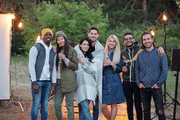 Mehrere liebevolle junge freunde in warmer freizeitkleidung, die in der reihe vor der kamera auf hintergrund der lichter und der grünen bäume stehen