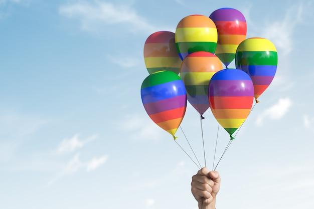 Mehrere luftballons mit lgbt-symbolen. hand hält sie. mit kopierplatz.