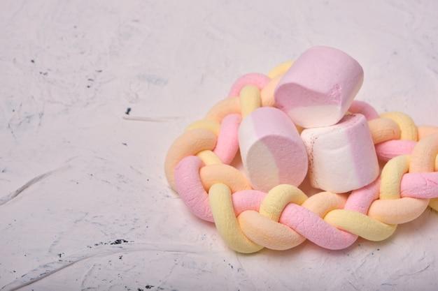 Mehrere marshmallows auf weißem hintergrund, lange geflochtene marshmallows, marshmallows mit fruchtaromen, kopierraum