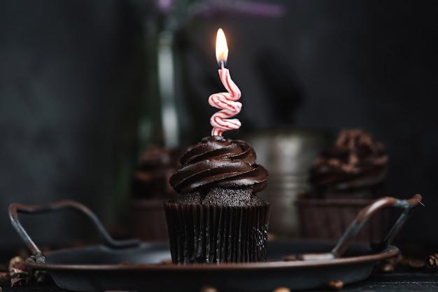 Mehrere muffins oder cupcakes mit schokoladenförmiger sahne am schwarzen tisch. festliche kerze brennt auf einem schokoladenkuchen.