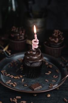 Mehrere muffins oder cupcakes mit schokoladenförmiger sahne am schwarzen tisch. festliche kerze brennt auf einem schokoladenkuchen
