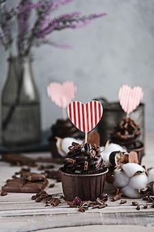 Mehrere muffins oder cupcakes mit schokoladenförmiger sahne am weißen tisch. eine karte in form eines herzens zum valentinstag. die hand einer frau zerbröckelt geriebene schokolade auf einem kuchen.