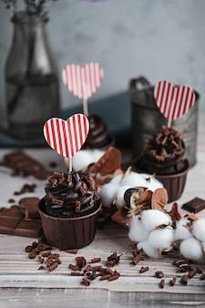 Mehrere muffins oder cupcakes mit schokoladenförmiger sahne am weißen tisch. eine weihnachtskarte in form eines herzens zum valentinstag in einem von ihnen.