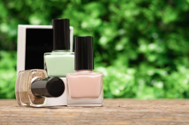 Mehrere nagellackflaschen im frühlingsgarten. satz nagellackflaschen auf holzschreibtisch auf grünem blattnaturhintergrund