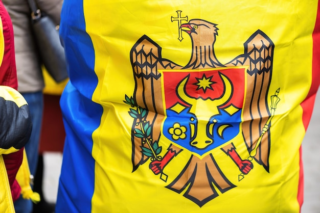 Mehrere nationalflaggen, menschen, die vor dem gebäude des verfassungsgerichts in chisinau, moldawien, für vorgezogene wahlen protestieren