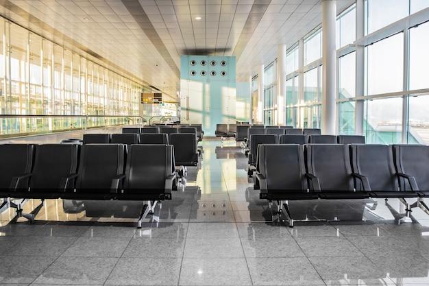 Mehrere reihen moderner schwarzer sitze in der leeren, sonnigen wartehalle des flughafens