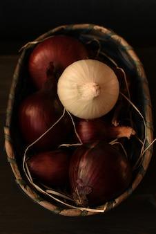 Mehrere rote spanische zwiebelköpfe und eine weiße zwiebel werden zu einem weidenkorb zusammengefaltet. dunkelbrauner hintergrund