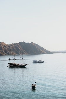 Mehrere schiffe an einer küste mit blick auf die hügel