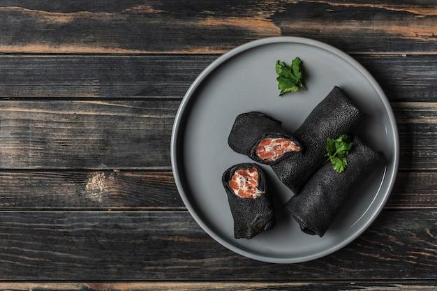 Mehrere schwarze tintenfischtintenpfannkuchen mit lachs- und käsefüllung auf einem grauen teller auf einem schwarzen hölzernen hintergrund. draufsicht. flach liegen.