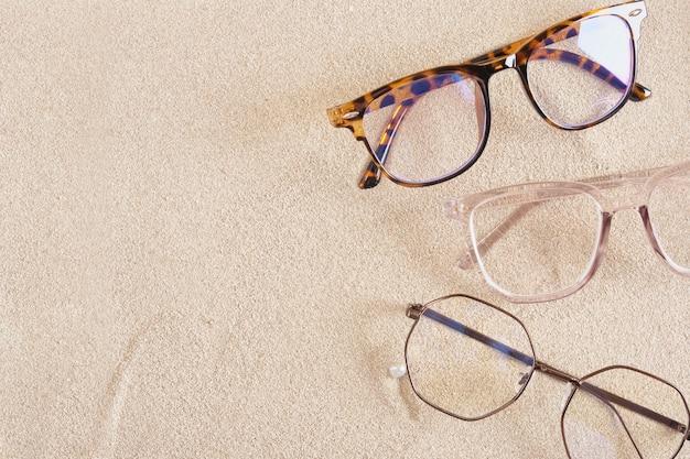Mehrere stilvolle brillen auf dem sand, draufsicht des kopierraums