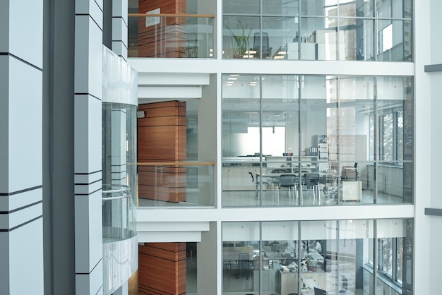 Mehrere stockwerke in einem großen, modernen businesscenter mit balkonen, fenstern und offenen büros mit möbeln